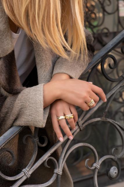 donna bionda indossa degli anelli su una scalinata